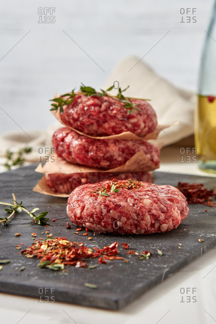 Homemade raw veal steaks cutlets are ready for frying or grill with paprika and olive oil on a black shale plate on a white background, place for text.