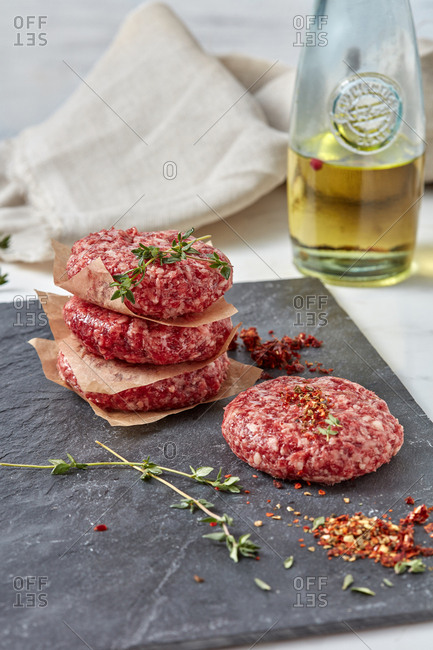 Ingredients for cooking homemade burgers - natural raw ground beef meat cutlets with herbs and spices on a black shale plate on a white background.