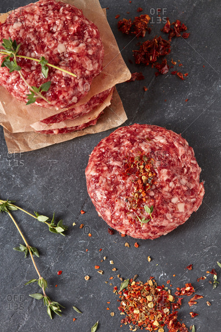 Ingredients for cooking homemade burgers - natural raw ground beef meat cutlets with herbs and spices on a black shale background. Flat lay.
