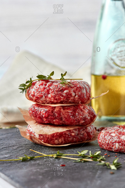 Fresh ground raw meat homemade cutlets with herb thyme, paprika, olive oil to prepare for frying on a black slate plate on a white background, place for text.