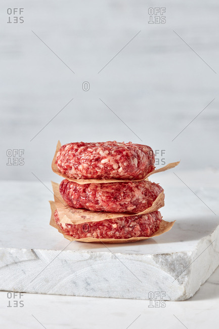 Organic raw ground beef, round patties for making homemade burger on a stone white marble cutting board, copy space.