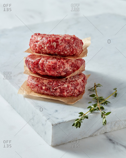 Raw veal meat cutlets steaks for cooking homemade burgers with thyme on a white marble board, stone background, place for text.