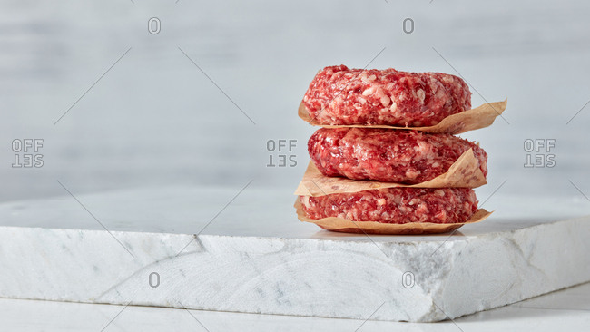 Homemade raw burgers - minced cutlets from organic beef meat for frying or grill on a white marble background, place for text.