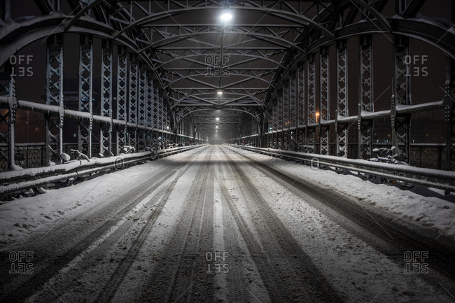 Direct view of empty roadway on a bridge in the snow