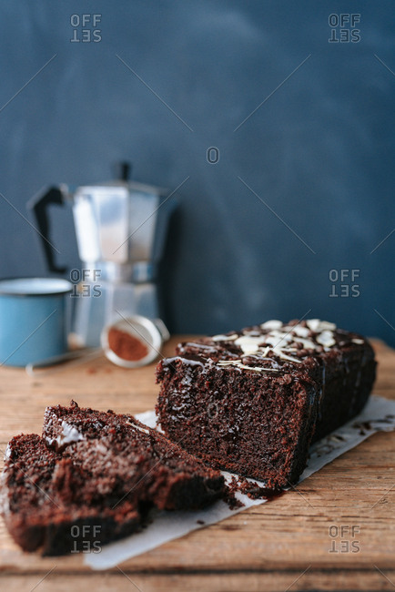Chocolate bread cake with cut slices on dark background