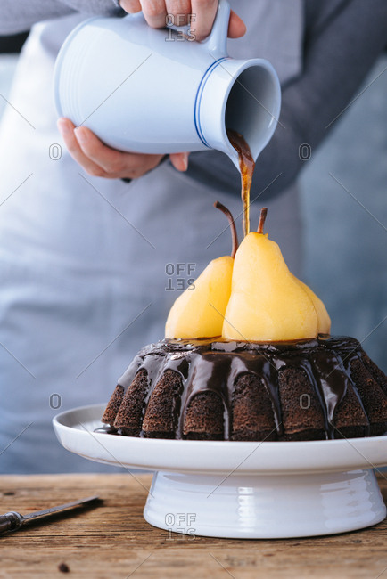 Person pouring sugar syrup on top of poached pears on a chocolate cake