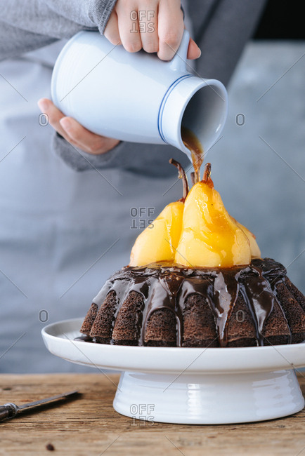Person pouring sugar syrup on top of pears on a chocolate cake