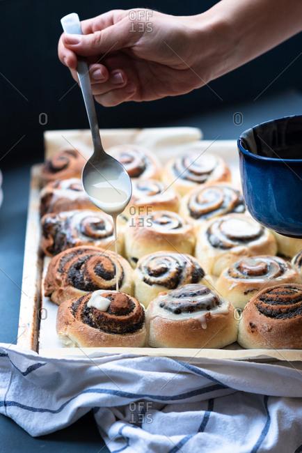 Baker drizzling glaze over poppy seed rolls