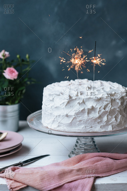 Birthday cake with two lit sparklers