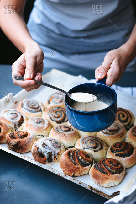 Person putting sugar glaze syrup on to baked poppy seed buns