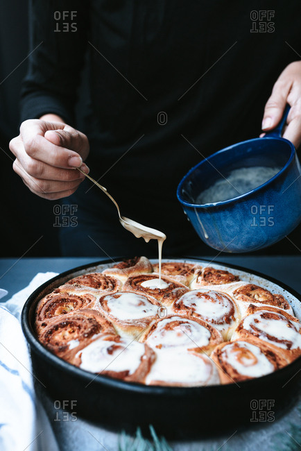 Person putting sugar glaze syrup on to baked cinnamon buns