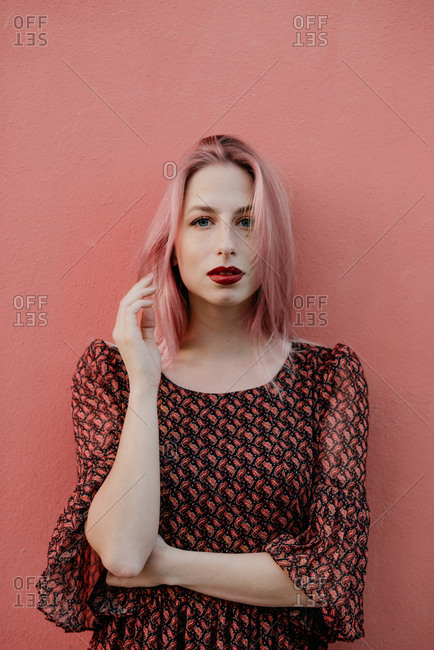 Portrait of young woman on pink background in boho dress