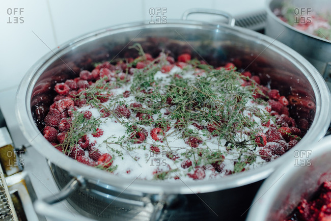 Raspberries in big soaking pot with sugar and spices for making jam