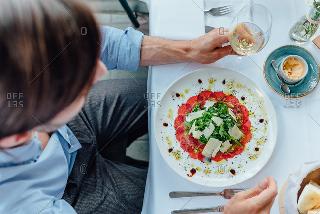 Man sitting at table with Carpaccio served in front of him