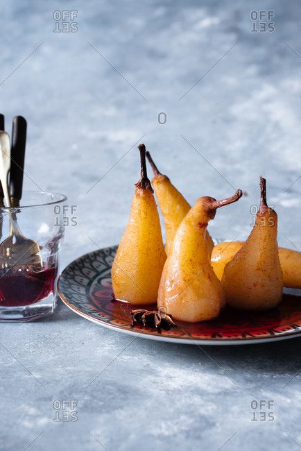 Poached pears on a plate with sugar syrup