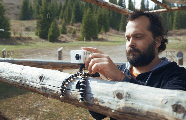 Bearded man at the mountain forest using video camera on tripod