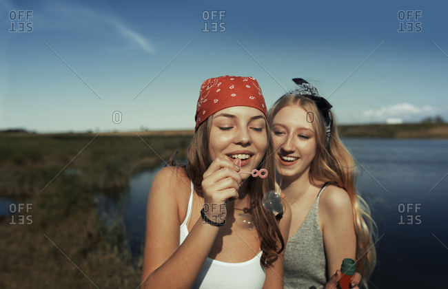 Two young teen girls blowing bubbles at the lake