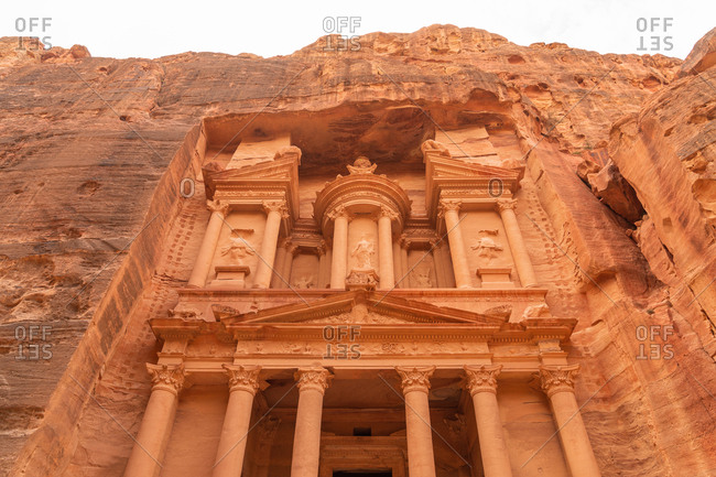From below view of facade of ancient temple carved in massive rocky cliff, Jordan