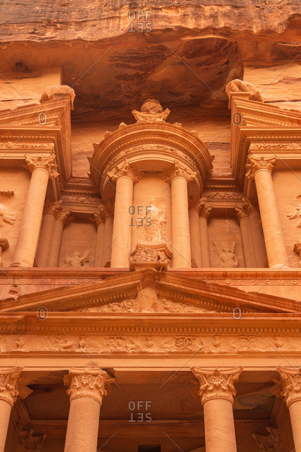 Exterior front of beautiful ancient temple carved in solid rocky cliff, Jordan