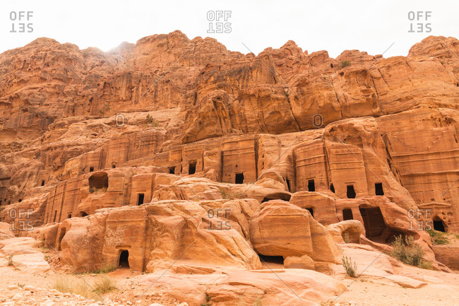 Exterior of dwelling site of ancient Petra city made in sandstone rocky cliffs, Jordan