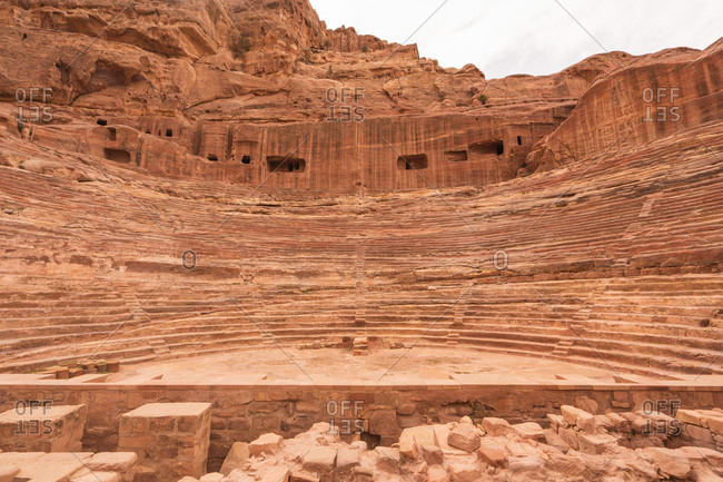 Remnants of beautiful amphitheater carved in solid cliff in Petra city, Jordan