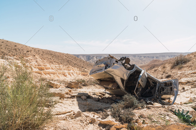 Panoramic view of wrecked car lying upside down on dry land of spacious desert in sunlight, Israel