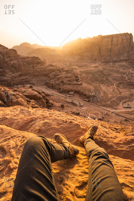 Crop feet of traveler sitting on sandstone rock high above ancient city of Petra in sunset light, Jordan