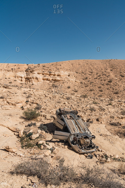 View of empty rocky hill with damaged wrecked car lying upside down in sunlight, Israel