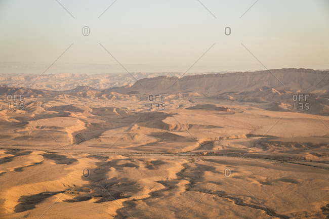 Landscape of sandy desert valley with rocks and trail in bright sunlight with haze