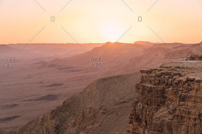 Panorama of empty dry desert with rough rocky cliffs on background of sunset sky, Israel