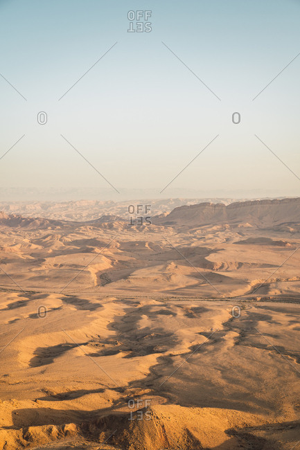 Perspective view of dry and hot Negev desert with sandy hills in sunny haze, Israel