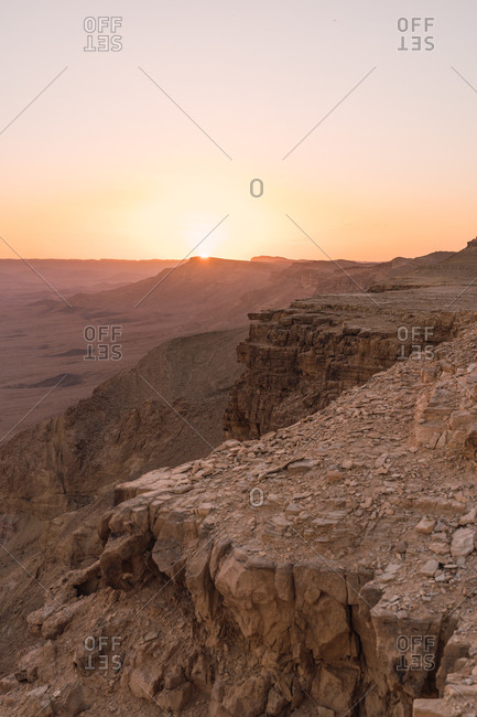 View of rocky cliffs in dry vast Negev desert with sunset sky on background, Israel