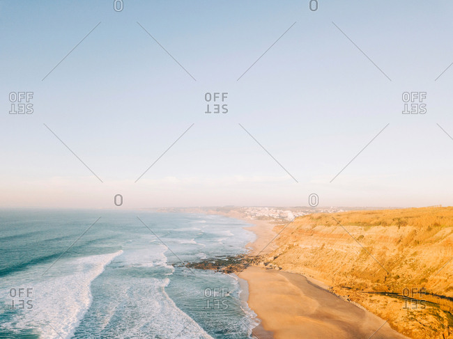 Beautiful drone view of sea water rolling on sandy coast on sunny day in amazing nature