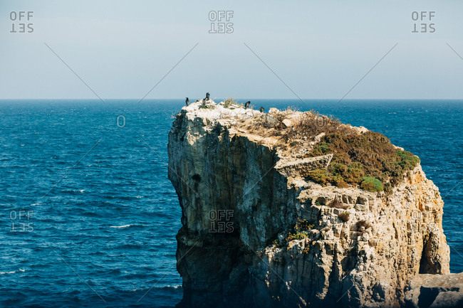Majestic drone view of rough rocky cliff located in beautiful rippling sea on sunny day in nature