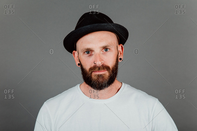 Bearded hairless hipster in t-shirt and hat on black background