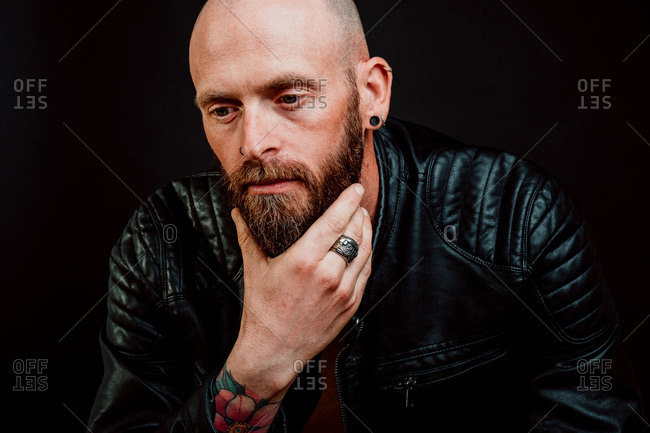 Thoughtful bald hipster in leather jacket with tattoos on hand scratching beard on black background