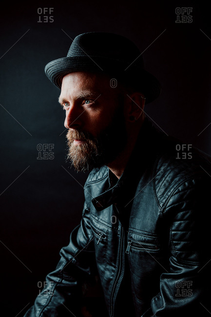 Cool hipster in hat and leather jacket looking away on black background