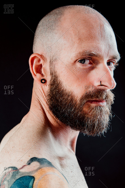 Side view of bald thoughtful hipster with earring and piercing looking away on black background