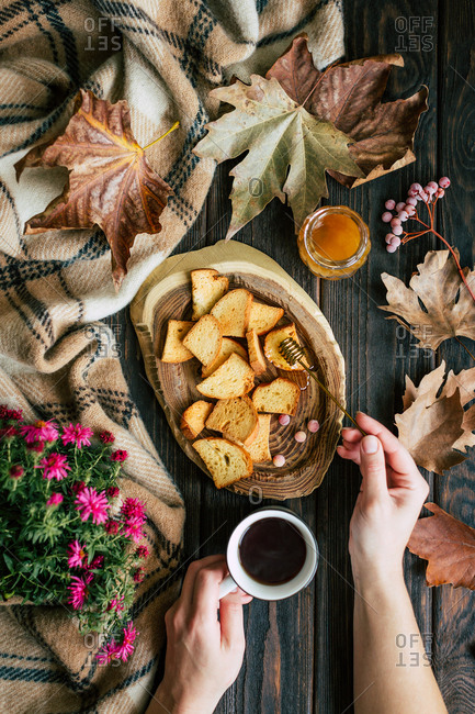 From above hands of anonymous woman holding cup of hot tea and spreading fresh honey on crunchy croutons near autumn leaves and flowers on lumber tabletop