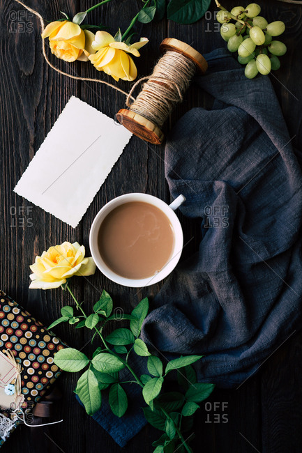 From above beautiful yellow roses and blank note lying near cup of fresh coffee on timber tabletop amidst piece of blue cloth with linen thread and ripe grapes