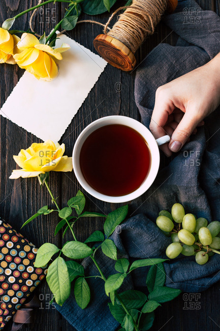 From above hand of anonymous female holding cup of aromatic tea near elegant yellow roses and empty note over wooden tabletop