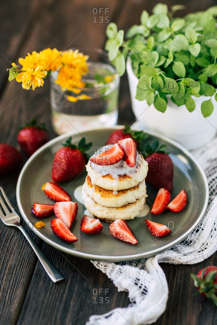 Delicious soft pancakes with fresh strawberries placed on ceramic plate near potted plant and glass with yellow flower