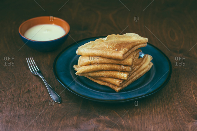 Bowl with tasty sauce placed near plate with pile of delicious blini on timber tabletop