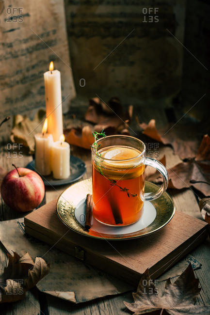 Cup of fresh tea with lemon placed near ripe apple and flaming candles amidst autumn leaves
