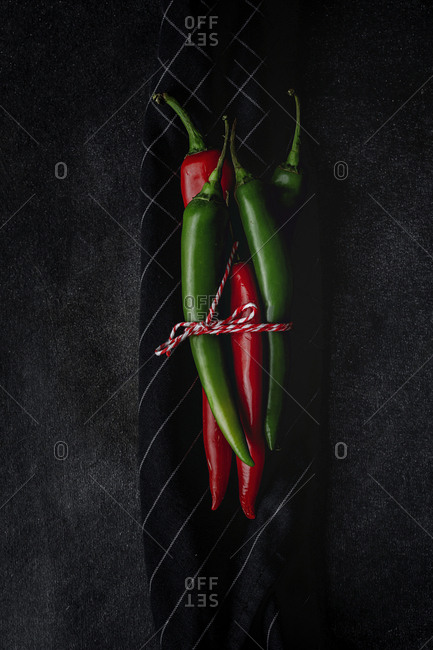 Fresh red and spicy chilli peppers on dark background. Flat lay. From above