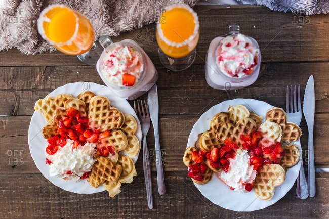 Appetizing waffles with jam and tasty drinks on tray on bed