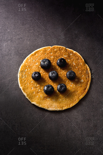 Closeup delicious pancake with ripe blueberries on dark gray tabletop