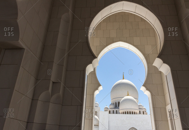 View of fantastic white palace through amazing arches on sunny day in United Arab Emirates