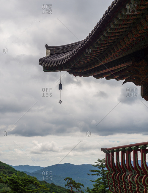 Beautiful roof of traditional Korean pagoda against overcast sky in mountainous terrain