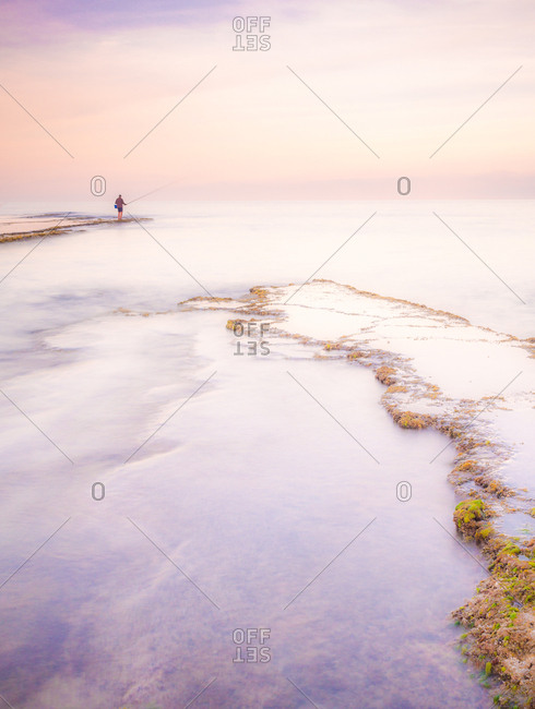 Distant unrecognizable person fishing while standing on rough coast of tranquil lake in morning